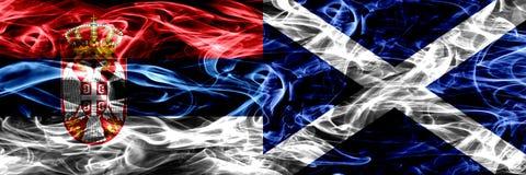 塞尔维亚对苏格兰,肩并肩被安置的苏格兰烟旗子 Th 免版税库存照片
