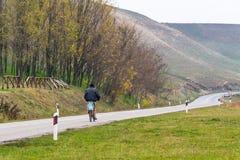 塞尔维亚路的一个孤独的骑自行车者 图库摄影