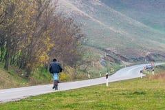 塞尔维亚路的一个孤独的骑自行车者 库存图片