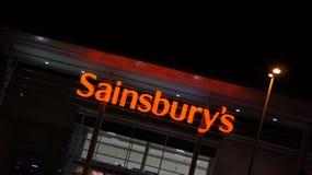 塞恩斯伯里的超级市场标志在晚上 免版税库存图片