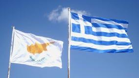 塞浦路斯旗子和希腊旗子拍动在风在杆 天空蔚蓝和塞浦路斯和希腊旗子 影视素材