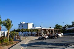 塞浦路斯, Ayia Napa, - 2015年9月20日:街道咖啡馆 人们食用在街道上的早餐停放方形字体自行车 免版税库存图片