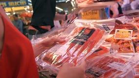 巴塞罗那,西班牙- 2016年6月10日:销售摊位用昂贵的西班牙火腿Jamon在La Boqueria市场上在巴塞罗那 影视素材