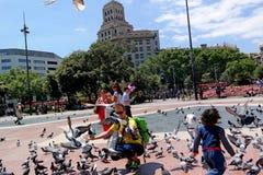 巴塞罗那,西班牙- 2014年5月17日:Placa Catalunya 喂养鸽子的游人 免版税图库摄影
