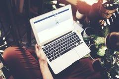 巴塞罗那,西班牙-01 02 2016年:人登记的facebook页 普通设计膝上型计算机在他的膝盖 社会网络屏幕 免版税库存照片