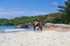 塞舌尔群岛,普拉兰岛- 8月03 :家庭沿Anse拉齐奥海滩走在2015年8月03日,塞舌尔群岛的普拉兰岛海岛 库存照片