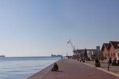 塞萨罗尼基,希腊- 2015年12月25日:放松在码头的人们-塞萨罗尼基旧港口的码头,希腊旗子可以是 库存照片