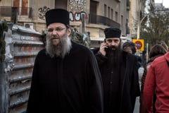塞萨罗尼基,希腊- 2015年12月24日:走在街道的两位希腊人Orrthodox教士塞萨罗尼基,一有电话c 库存照片