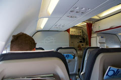 塞萨罗尼基,希腊- 2016年10月15日:飞机客舱,业务分类内部位子,在起飞以后的乘客 图库摄影