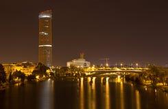 塞维利亚-对瓜达尔基维尔河河和现代Torre Cajasol的外型在晚上 免版税库存照片