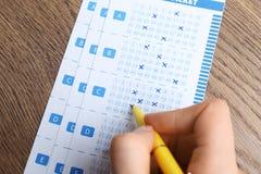 填好彩票的妇女用在木桌上的笔 免版税库存照片