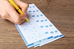 填好彩票的妇女用在木桌上的笔 免版税库存图片