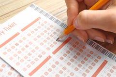 填好彩票的妇女用在木桌,特写镜头上的铅笔 免版税图库摄影