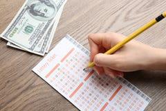 填好彩票的妇女用铅笔和金钱在木桌上 免版税库存照片