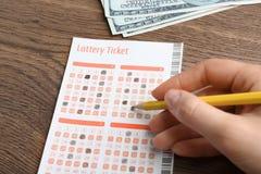 填好彩票的妇女用铅笔和金钱在木桌上 库存照片