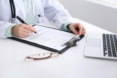 填好申请表的一位女性医生的特写镜头,坐在桌上在医院 免版税库存照片