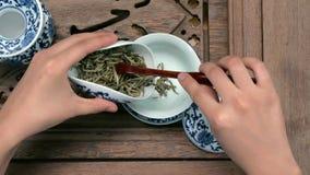 填装一个棕色茶壶通过漏斗 瓷中国杯子,钢茶匙 黑,绿色, puerh, oolong, tieguanyin 股票录像