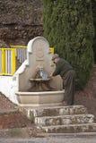 填装一个瓶在喷泉的饮用水的老人 免版税库存图片