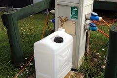填装一个饮用水容器在露营地浇灌和电力供应点 库存照片