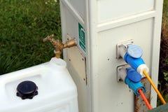 填装一个饮用水容器在露营地浇灌和电力供应点 图库摄影