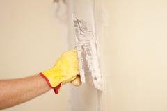 与刮板和水泥的家庭墙壁整修 免版税库存图片