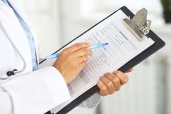 填装医疗形式的一位女性医生的特写镜头在剪贴板,当站立直接在医院时 免版税库存照片