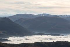 填装在有些山和小山之间的薄雾一个谷 免版税库存图片