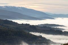 填装在有些山和小山之间的雾和薄雾一个谷 免版税库存照片