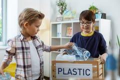 填装垃圾豆的勤勉小男孩用塑料垃圾 免版税库存照片
