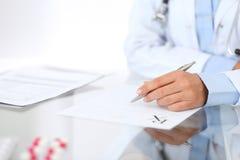 填装处方形式的医生妇女,当坐在医院特写镜头时的书桌 医师在工作和准备好t 免版税库存图片