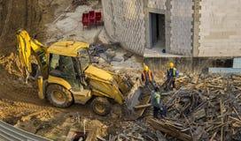 填装推土机的工作者用桶提与木小块 免版税库存图片