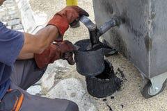 填装沥青桶的工作者从熔化的沥青的锅炉 图库摄影