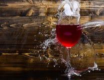 填装用水的葡萄酒杯与在黑暗的木背景飞溅 玻璃用倾吐与液体的酒与飞溅 免版税图库摄影