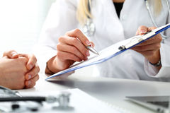 填装病史名单的女性医生手举行银笔 免版税图库摄影