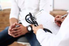 填装病史名单的男性医生手举行银笔 图库摄影