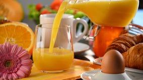 填装的玻璃用在桌上的橙汁与早餐 影视素材