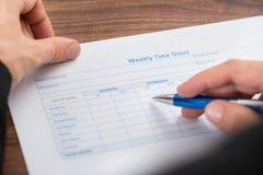 填装空白的每周工时表的人的手 免版税库存图片