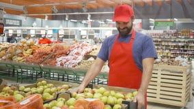 填装箱子的愉快的超级市场干事用在菜部门的梨 股票录像