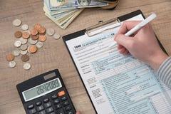 填装美国1040税的男性 免版税库存图片