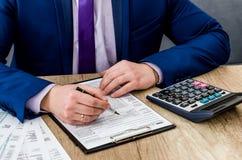 填装1040报税表的男性会计 免版税库存图片