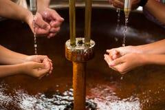 填装他们的手的人们用矿泉水 图库摄影