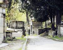 墓碑在黄昏的公墓,哥特式样式横渡夏天 库存图片