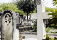 墓碑在黄昏的公墓,哥特式样式横渡 免版税库存照片