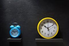 墙壁和闹钟在黑背景 库存照片