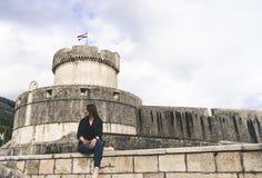 墙壁的外视图在杜布罗夫尼克(附近的;Croatia);亚得里亚海的城市 坐在墙壁的女孩游人 库存图片