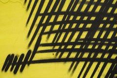 墙壁的抽象片段有街道画,老切削的油漆,抓痕,难看的东西纹理,黄色黑颜色细节的  免版税库存图片