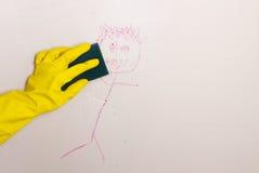 墙壁的清洁蜡笔与海绵 免版税库存照片