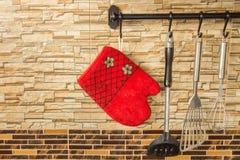 墙壁表面上垂悬的厨房手套 免版税库存照片