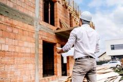 墙壁,在工地工作的基础设施 建筑工程师读的计划,运作在大厦工地工作 免版税库存照片