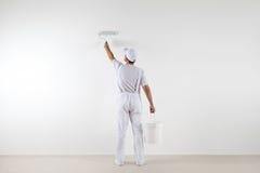绘墙壁,有漆滚筒的画家人背面图  免版税库存图片